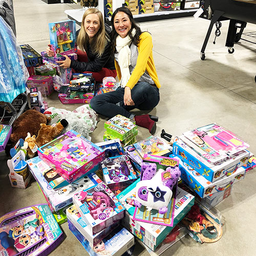 Heidi Jarett (left) and Monica Alters (right) sort through their great finds after the 2018 Toy Sale.